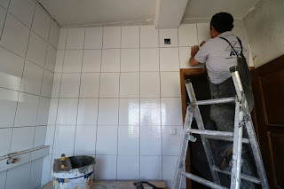 Final tiles go onto this wall