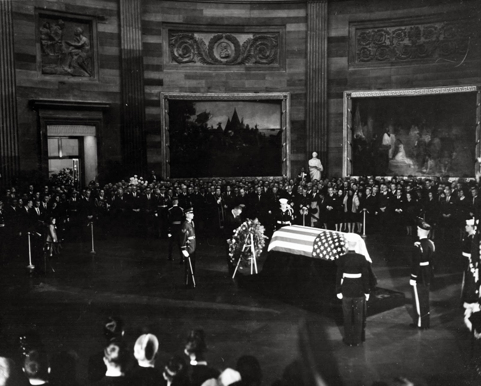 President Lyndon B. Johnson placing a wreath before the flag-draped casket of President Kennedy.