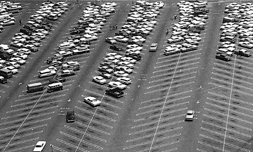 a photograph of a 1960s shopping mall parking lot