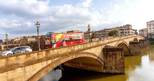 Ônibus turístico passando por ponte em Florença