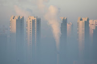 A chimney is seen in front of residential buildings during a polluted day in Harbin, Heilongjiang Province, China, January 21, 2016. (Credit: Reuters/Stringer) Click to Enlarge.