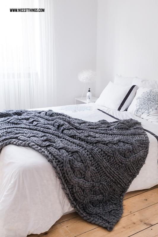 Schlafzimmer mit weißer Bettwäsche und gestrickter Tagesdecke Chunky Knit