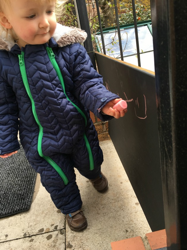 toddler chalking on blackboard