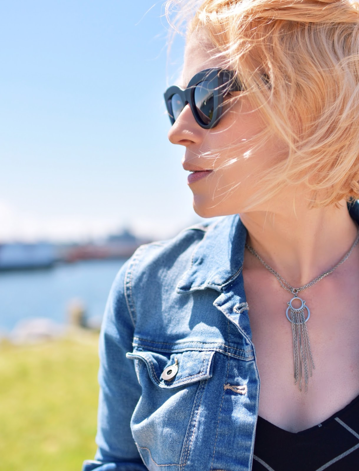 denim jacket, cat-eye sunglasses, tassel necklace