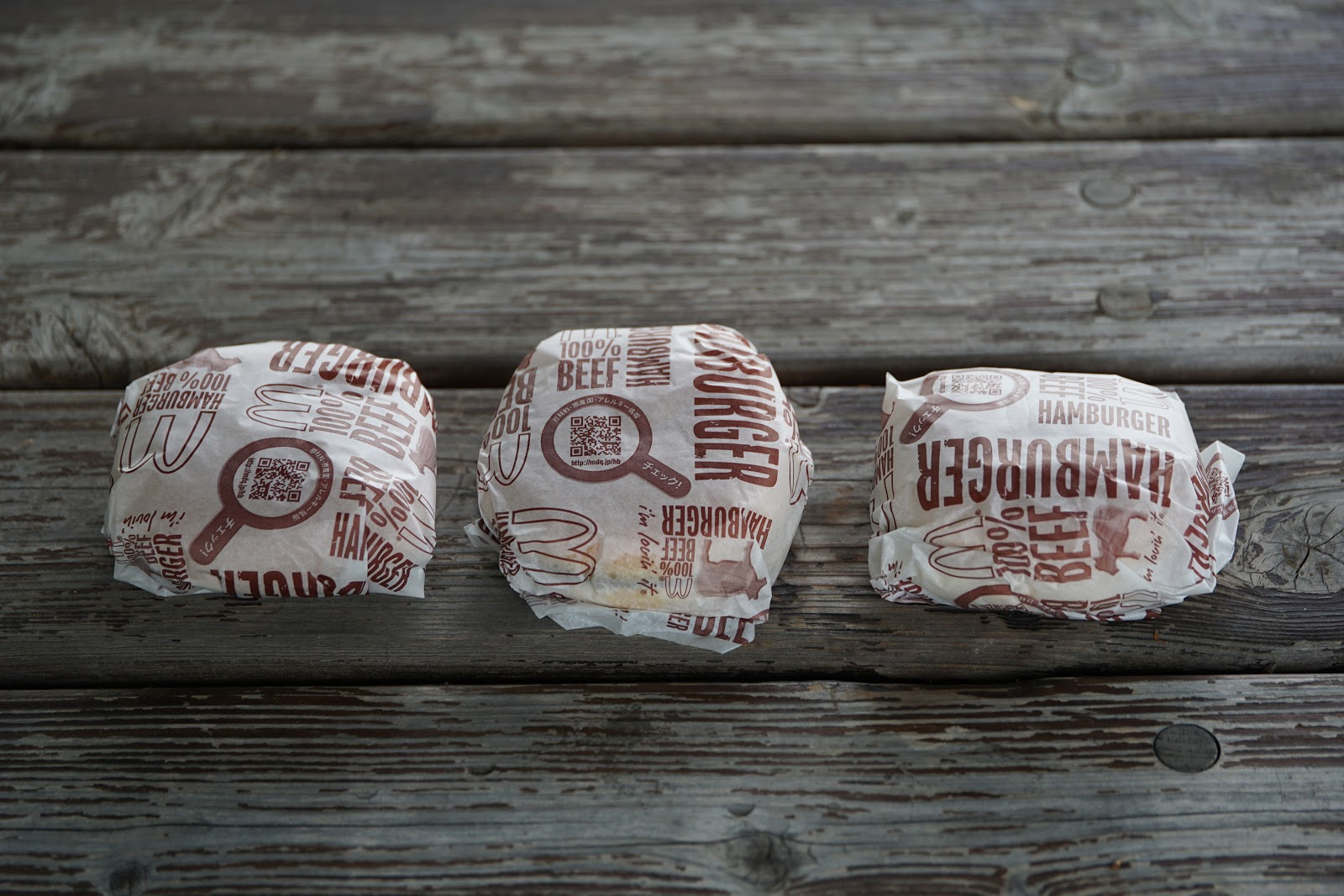 木の机の上の三つ並んだ紙包みのハンバーガー