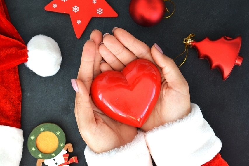 Hands holding Heart decoration alongside Santa hat