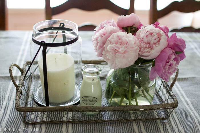 Fresh peonies from the garden in chicken wire basket in farmhouse style dining room