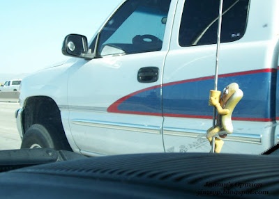 Hot dog antenna topper viewed through windshield with pickup truck in background.