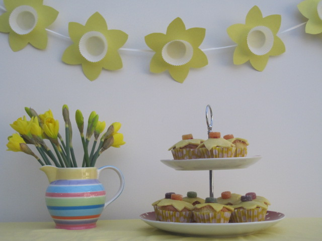 Daffodil bunting, with a jug of daffodils and a tiered cake stand filled with cakes