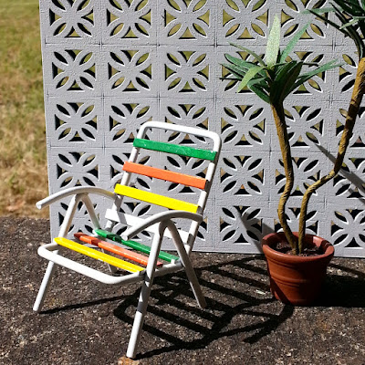 One-tweltfh scale modern miniature garden chair and plant in front of a miniature breeze block wall.