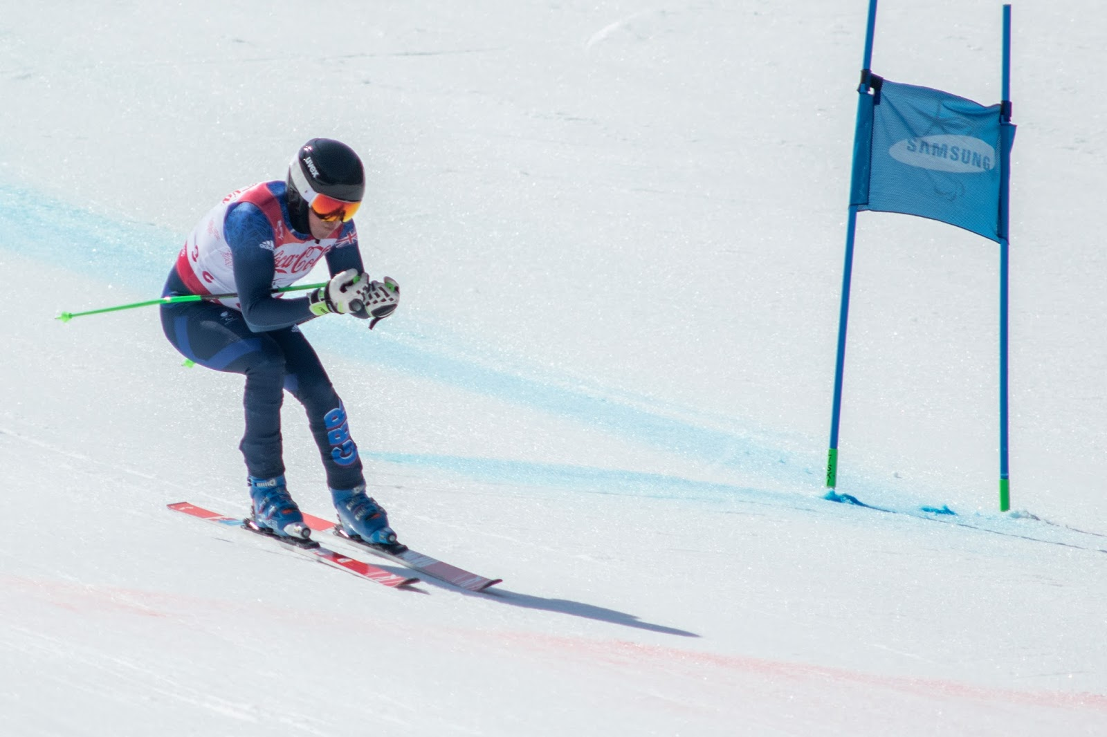 Man is skiing down a hill, wearing a blue ski suit with red skis and green ski poles.