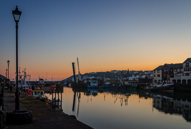 Photo of reflections on the still waters of Maryport harbour at sunrise