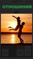 На фоне заходящего солнца на берегу мужчина руками поднял девушку высоко над собой