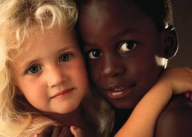 Picture of a white and black child hugging.