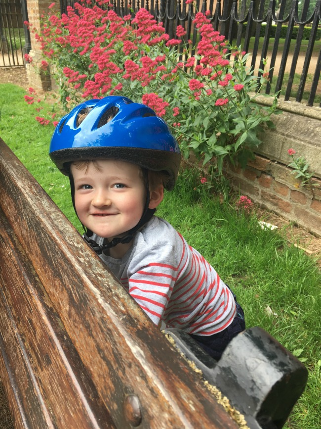 toddler-grinning-behind-a-bench-at-Tredegar-park
