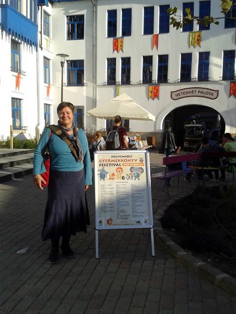 Ecsédi Orsolya a Városligetben, a Holnemvolt Gyermekkönyv Fesztiválon, az esemény programját tartalmazó plakát mellett.