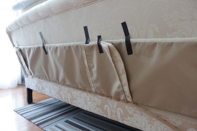 attaching tape to hold sofa's skirt up