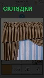 На окне висят серые шторы собранные в складки по всей своей длине на карнизе