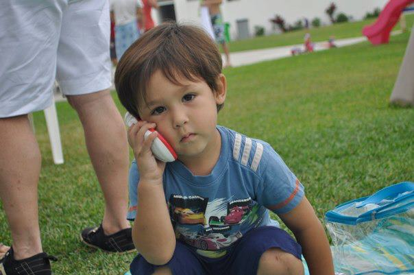 Beautiful brown eyed boy 2 years age holding phone loking bored and cute
