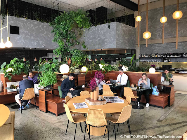 Guests drinking coffee and working on their laptops in a cafe