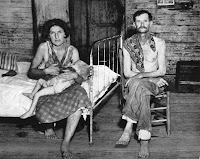A black and white photograph of a shirtless man seated next to a bad on which a seated woman nurses a toddler.