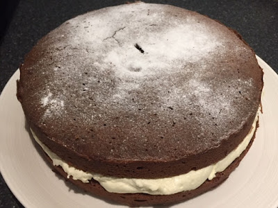 Finished Chocolate Sandwich Cake with whipped cream filling on a white plate