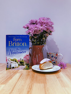 fern britton's the newcomer book alongside a bunch of flowers and an iced bun