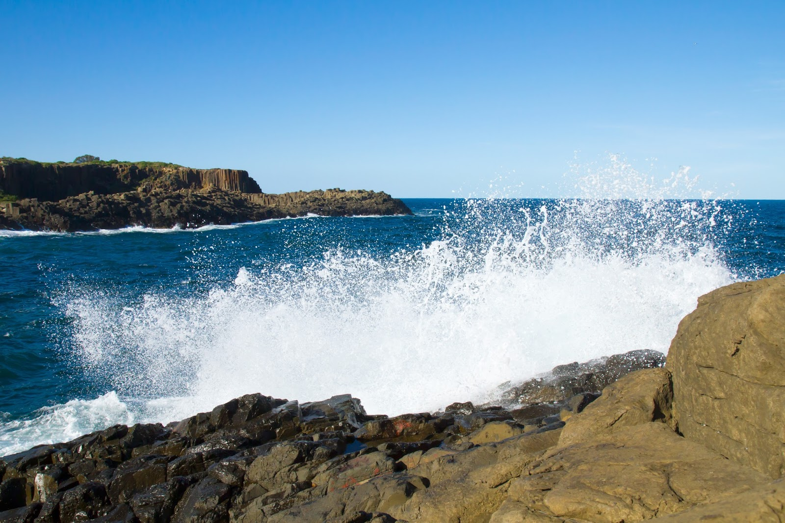 waves crashing at the bombo rock quarry in australia