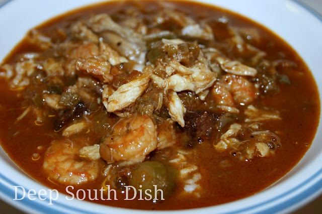 A seafood gumbo made with a dark roux, a rich shrimp stock, the Trinity of vegetables, tomatoes, andouille and shrimp, crab and oysters.