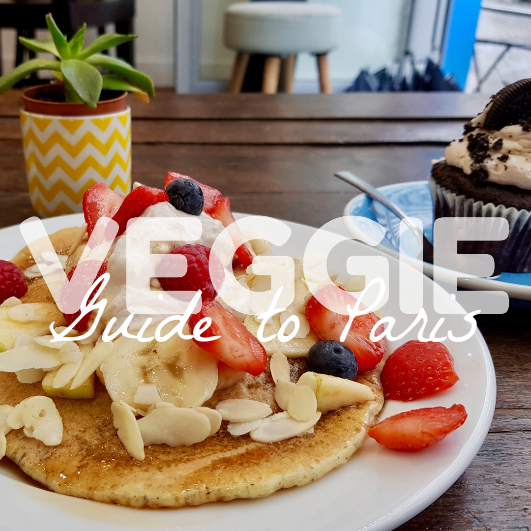 a stack of pancakes, topped with fruit, sit on a wooden table, cupcake with Oreo on top in background