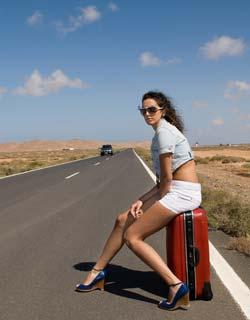 mulher com mala na beira da estrada