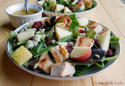 side view of bowls of fall dinner salad with chunks of apple, chicken, cranberries, cheese and homemade vinagriette