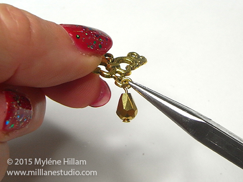 Attaching the gold teardrop bead to the bottom of the gold connector with chain nose pliers.