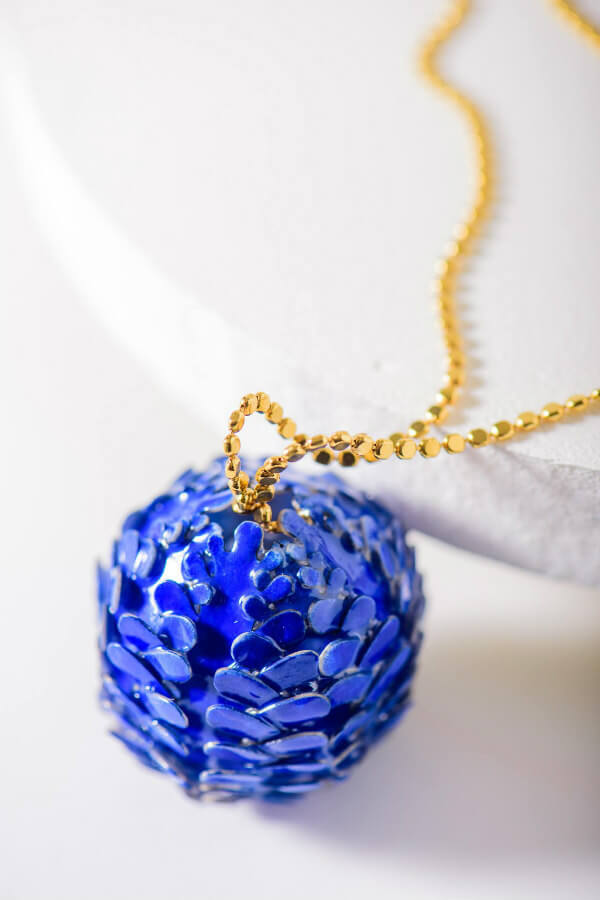 blue ball made of paper on gold necklace chain