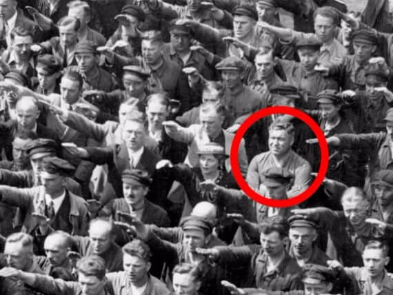 One man in crowd, circled in red, won't raise the Nazi salute