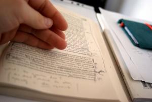 A imagem mostra um estudante que olha um livro pesadamente anotado.