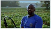 Rev. Richard Joyner smiles at camera while standing in a field of healthy crops