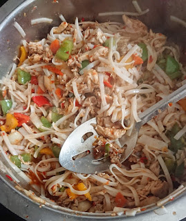 adding rice noodles to the vegetables and chicken mixture