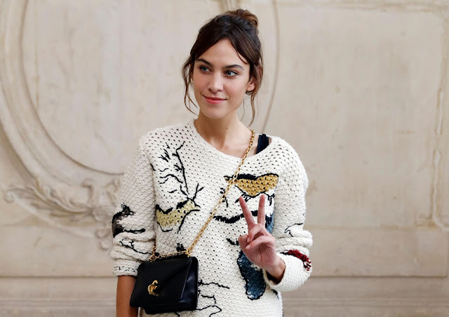 girl in a white appliqued sweater, black cross-body bag, and hair in an up-do