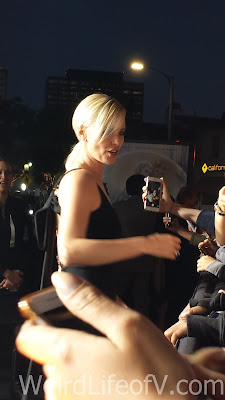 Charlize Theron posing with fans in the fan pit