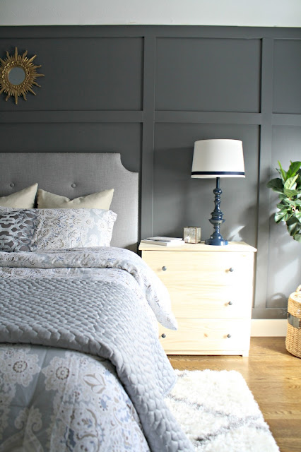 Dark paneled accent wall behind bed