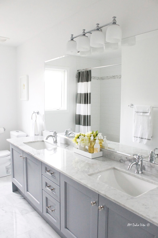 White and grey bathroom with striped shower curtain.