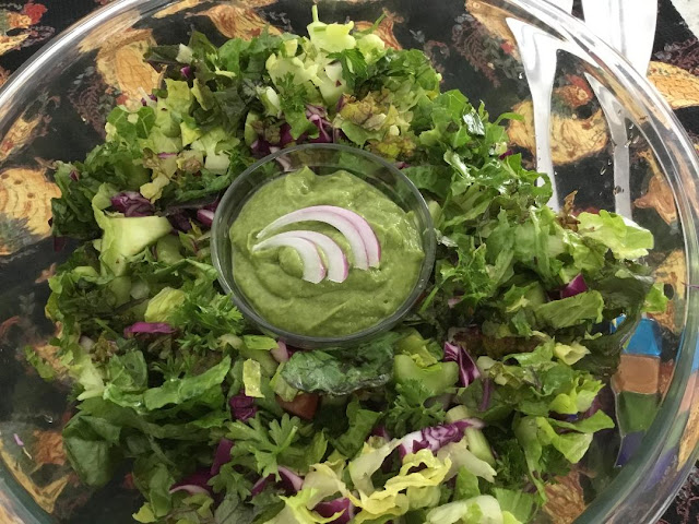 large bowl of salad with green dressing
