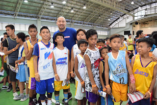 Alaska Coach Jeffrey Cariaso poses with Jr NBA players