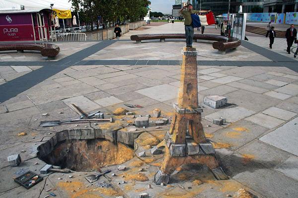 Kazılan toprak ve taşlarla yapılmış bir Eyfel kulesini gösteren kaldırım sanatı resmi