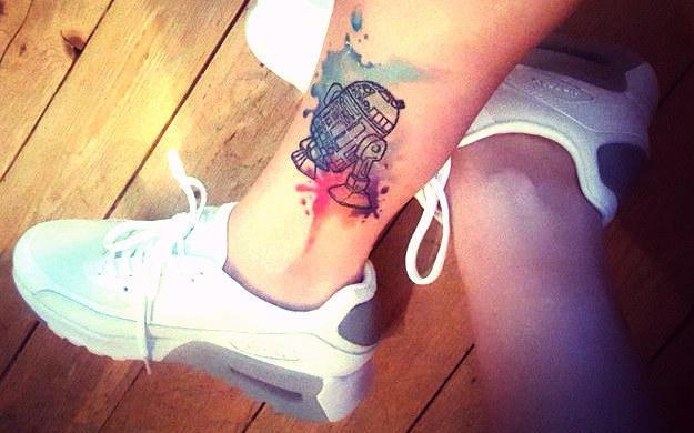 Tatuaje geek de RD-D2 en la pantorrilla de una joven