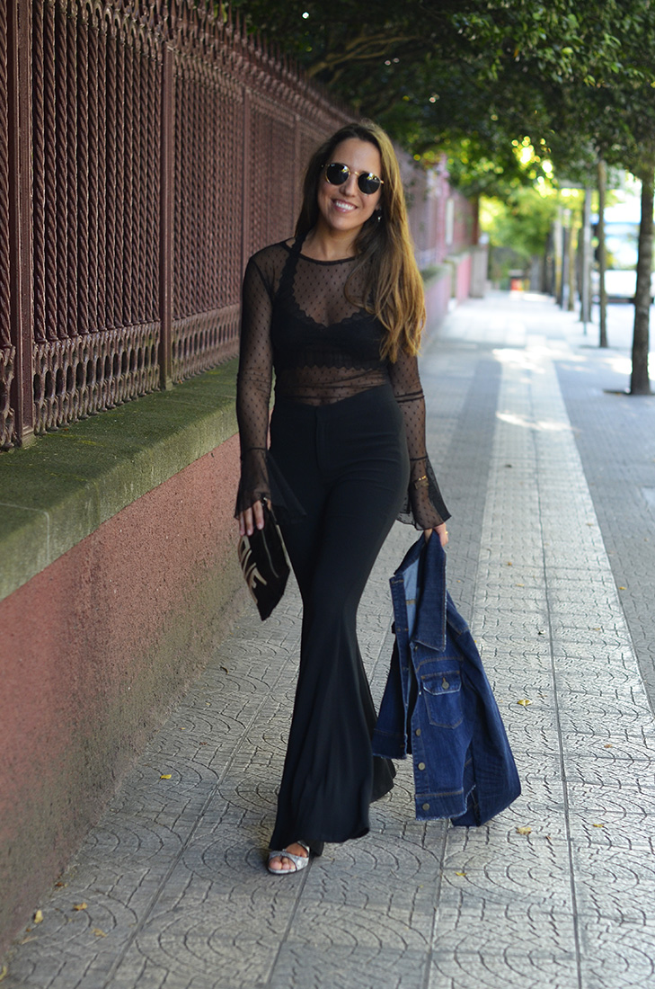 Streetstyle - Wearing flare pants, denim jacket, sheer top, ray ban round sunglasses and Love clutch