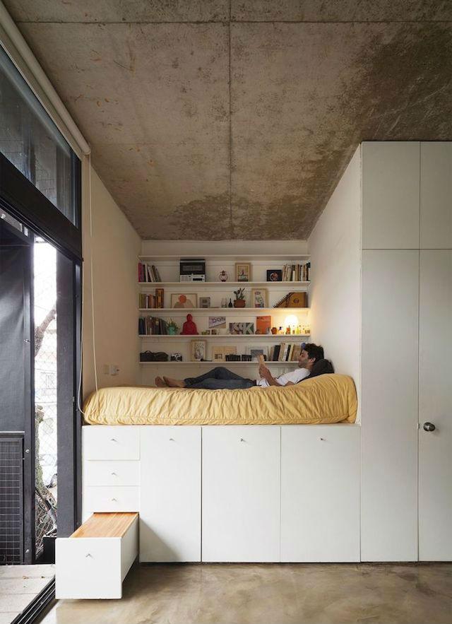 cama elevada sobre estructura de madera con cajones y armarios sin tiradores