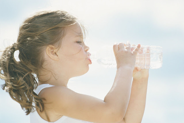 little girl holding a bottled water