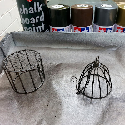 Two painted wire items on a sheet of baking paper in a box, with a row of various spray cans lined up behind in browns, greys and metal colours.